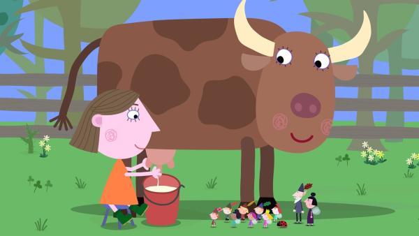 Lucie zeigt den Elfen und Feen, wie eine Kuh gemolken wird. | Rechte: ZDF/Astley Baker Davies Ltd/Rubber Duck Entertainment