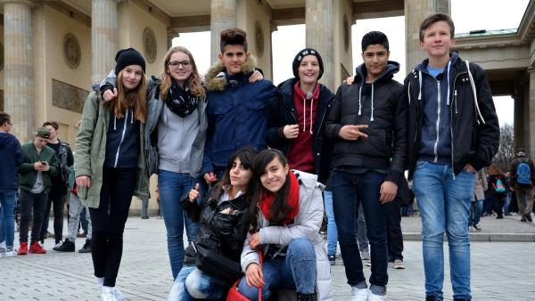 Die acht Jugendlichen haben sich gerade erst kennengelernt und wollen nun Berlin erobern. Sie fangen erstmal beim Brandenburger Tor an.  Spaß haben sie jetzt schon:  Malina, Millane, Akram, Linus, Seyid, Oscar (von links nach rechts, stehend),  Bayan und Rashad (vorne). | Rechte: ZDF/IMAGO TV