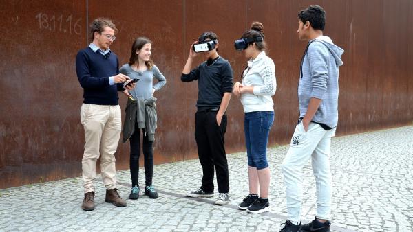 Treffpunkt Berliner Mauer: Mit einer VR-Brille tauchen Clara, Elvis, Manar und Milad (v.l.n.r.) in das geteilte Berlin der 60er Jahre ein. Die geflüchteten Jugendlichen berichten dabei über ihre Erlebnisse während der Flucht nach Deutschland. | Rechte: ZDF/Imago TV