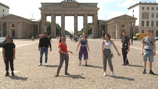 Die sieben von 'Berlin und wir! Spezial' vereint mit Abstand vor dem Brandenburger Tor. Die Jugendlichen haben gemeinsam die Prüfung zum Mofaführerschein absolviert. Dabei gab es Gelegenheit sich über Herausforderungen von Schulprüfungen zu unterhalten und das Leben als Geflüchtete in Berlin. (Hassan A., Seyid, Narges, Lilli, Manar, Hassan S., Aurel) | Rechte: 76726-0-1