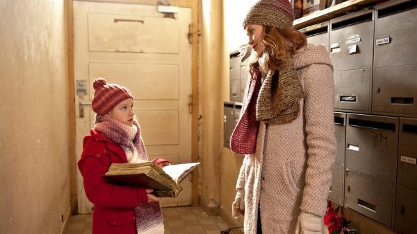 Paule (Chloé Heinrich) findet im Altpapier ein geheimnisvolles Weihnachtsbuch. Sie fragt ihre Mama (Inez Bjørg David), ob sie es behalten darf. | Rechte: KiKA/WunderWerk/Britta Krehl
