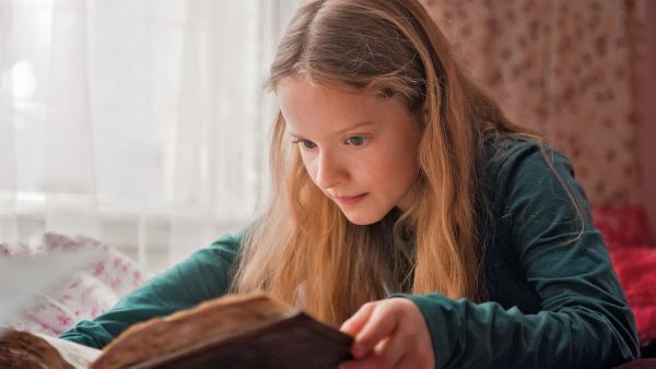 Paule (Chloé Heinrich) liest in dem geheimnisvollen Weihnachtsbuch und erfährt von der Wahl eines neuen Weihnachtsmanns.   Rechte: KiKA/WunderWerk/Britta Krehl