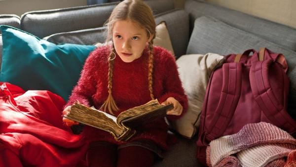 Paule (Chloé Heinrich) liest im geheimnisvollen Weihnachtsbuch, wie der wahre Weihnachtsmann aussieht. | Rechte: KiKA/WunderWerk/Britta Krehl