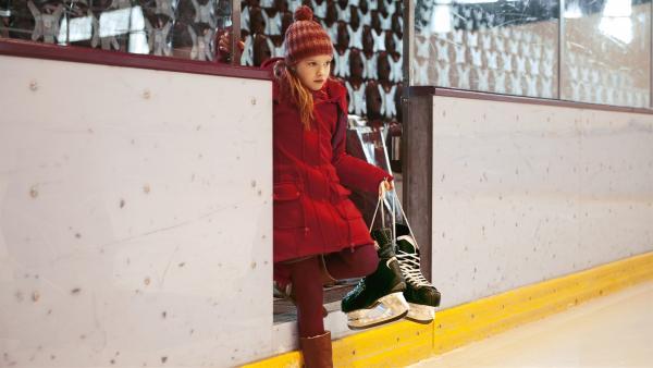 Auf der Suche nach Schuhen aus der Vergangenheit wagt sich Paule (Cloé Heinrich) zum ersten Mal seit langem wieder in die Eishalle. | Rechte: KiKA/WunderWerk/Britta Krehl