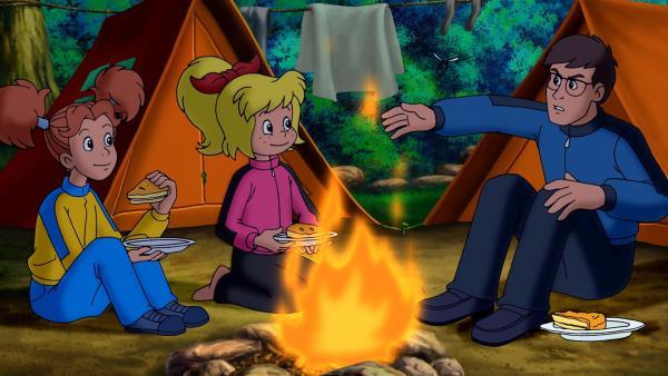 Bibi Blocksberg und ihre Freundin Marina beim abendlichen Lagerfeuer mit Papa Bernhard Blocksberg. | Rechte: ZDF/KIDDINX Studios GmbH