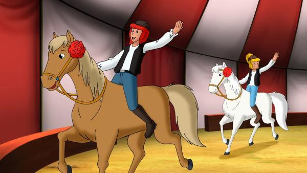Tina (l.) und Bibi (r.) springen beherzt als Ersatznummer im Zirkus Magnus ein und zeigen ihre Reitkünste. | Rechte: ZDF/Kiddinx - Berlin