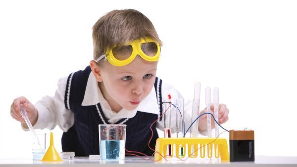 Junge mit gelber Schutzbrille schaut gespannt auf Reagenzgläser und spielt Labor