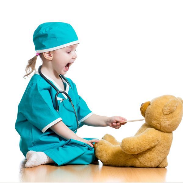 Mädchen als Ärztin verkleidet mit einem Teddybär als Patient
