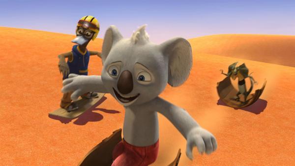 Jauchzend surfen Blinky, Jacko und Daredevil Dave die Sandpiste runter, um Crankys Sandraub zu stoppen.   Rechte: KiKA/Studio 100 Media / Flying Bark