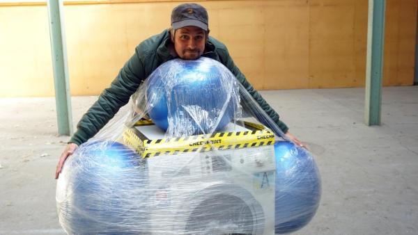 Tommy Scheel trägt eine mit Gummibällen umwickelte Waschmaschine. | Rechte: ZDF