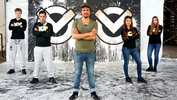 Tommy und sein Team stehen mit verschränkten Armen vor dem Checkpoint-Logo. Es ist mit Farbe beschmiert. | Rechte: ZDF