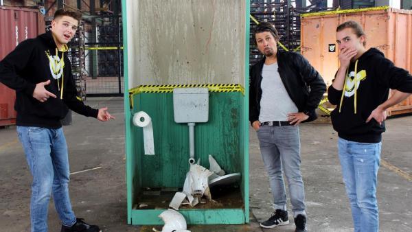 Tommy und das Team stehen um eine demolierte Kloschüssel herum. | Rechte: ZDF