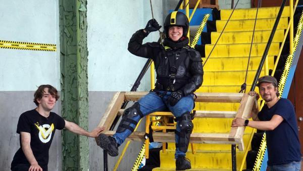 Checkpoint: Tommy und das Testteam stehen an einer Treppe. Ein Checkpoint-Mitglied schwebt in einem Gurt über der Treppe.  | Rechte: ZDF