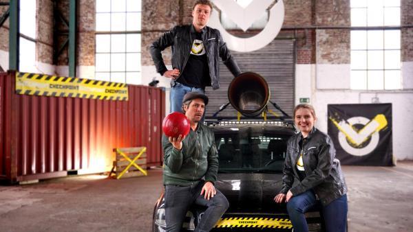 Checkpoint: Tommy und sein Team stehen um ein präpariertes Auto herum. Tommy hat eine rote Bowlingkugel in der Hand. | Rechte: ZDF