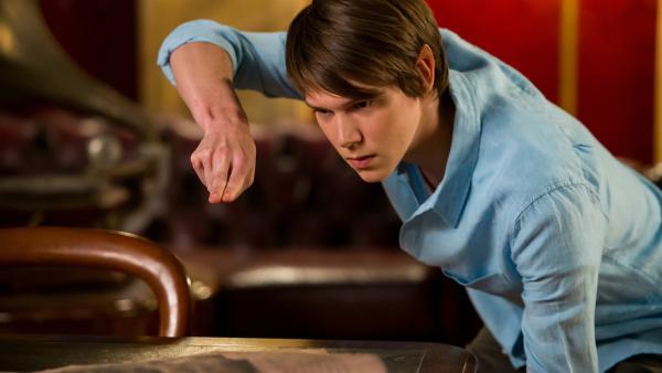 Darra (Julian Cullen) versucht verzweifelt, die Hausaufgabe von Professor Maxwell zu erfüllen. Er soll einen kleinen Elefanten aus einem magischen Buch zaubern.   Rechte: ZDF/Jonathan M. Shiff Productions/Screen Queensland