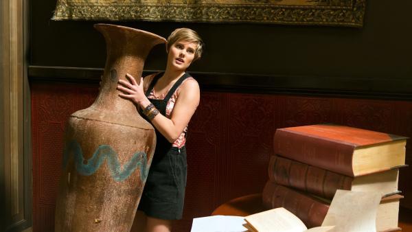 Imogen (Elizabeth Cullen) braucht ein Gefäß, um den magischen Stuhl einzufangen. Doch die große Amphore ist zu schwer. | Rechte: ZDF/Jonathan M. Shiff Productions/Screen Queensland