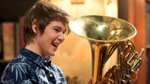 Darra (Julian Cullen) hat ein magisches Horn in der Bibliothek gefunden. Dieses wird später bei der Suche nach dem verschwundenen Postboten noch gute Dienste leisten. | Rechte: ZDF/Jonathan M. Shiff Productions/Screen Queensland