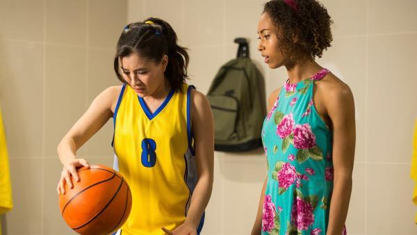Kyra (Kimie Tsukakoshi links) stellt erstaunt fest, dass der Basketball an ihren Fingern festzukleben scheint. Hier kann nur Magie im Spiel sein. Ruksy (Rainbow Wedell rechts) ist auch dieser Meinung. | Rechte: ZDF/Jonathan M. Shiff Productions/Screen Queensland