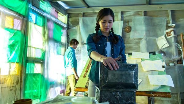 Kyra (Kimie Tsukakoshi rechts) und Darra (Julian Cullen links) durchsuchen ein Strandhaus. Hier hatte der verschwundene Architekt der Bibliothek sein Atelier.  Eine leere Schatulle fasziniert Kyra.   Rechte: ZDF/Jonathan M. Shiff Productions/Screen Queensland