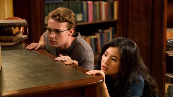 Kyra (Kimie Tukakoshi, rechts) hat Peter (Jamie Carter, links)  heimlich mit in die Bibliothek genommen. Als sie Geräusche hören, verstecken sie sich. Sie wollen nicht entdeckt werden. | Rechte: ZDF/Jonathan M. Shiff Productions/Screen Queensland