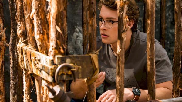 Peter (Jamie Carter) wurde durch magische Kräfte in ein Märchenbuch gezogen und dort von zwei ungehobelten Holzfällern  in einen Holzkäfig gesperrt. Er hat keine Ahnung, wie er wieder aus dieser misslichen Lage herauskommen soll. | Rechte: ZDF/Jonathan M. Shiff Productions/Screen Queensland