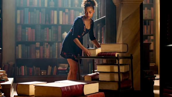 Ruksy (Rainbow Wedell) sucht in den Büchern der Bibliothek nach einem Hinweis, wieso Kyra ihre magischen Kräfte nicht mehr richtig kontrollieren kann. | Rechte: ZDF/Jonathan M. Shiff Productions/Screen Queensland
