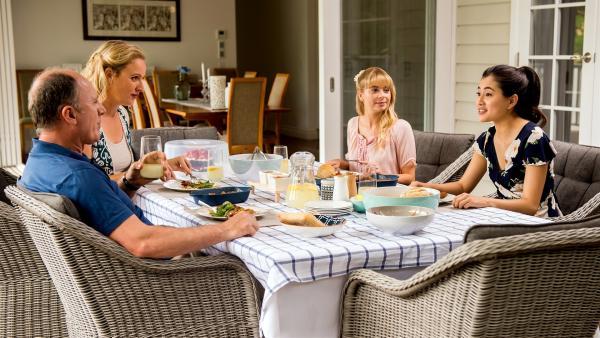Kyra (Kimie Tsukakoshi, rechts) ist bei Lily (Mia Milnes, 3.von links) und ihren Eltern Sean (Nicholas Bell. links) und Ella (Samantha Fitzgerald, 2.von links) zum Essen eingeladen. | Rechte: ZDF/Jonathan M. Shiff Productions/Screen Queensland
