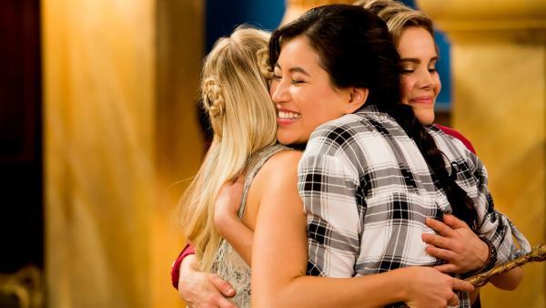 Kyra (Kimie Tsukakoshi, Mitte) umarmt voller Freude ihre Freundinnen Lily (Mia Milnes, links) und Imogen (Elizabeth Cullen, rechts). Sie hat ihre Erinnerungen an die magische Welt wieder zurück und auch ihre magischen Kräfte.   Rechte: ZDF/Jonathan M. Shiff Productions/Screen Queensland