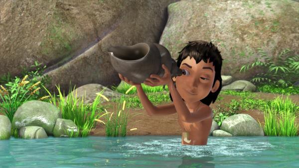 Mogli hat im Fluss ein großes Schneckengehäuse gefunden. Wenn er hineinbläst, ertönt ein Geräusch, das sich anhört, wie der Ruf eines Kranichs. | Rechte: ZDF/DQ Entertainment