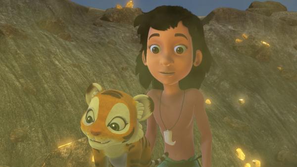 Mogli (r.) hat das weggelaufene Tigerjunge Chota (l.) gefunden. Sie stehen im Krater, der beim Aufprall der Sternschnuppe entstanden ist. Überall funkelt der Sternenstaub. | Rechte: ZDF/DQ Entertainment