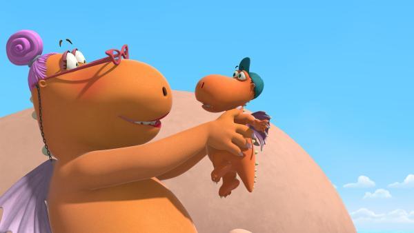 Ganz verzückt blickt Lehrerin Proselinde den kleinen Drachen Kokosnuss an, den sie hochgehoben hat und vor sich in den Händen hält. | Rechte: ZDF/Caligari Film