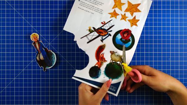 Die Bilder auf der Anleitung werden mit einer Schere ausgeschnitten. | Rechte: KiKA
