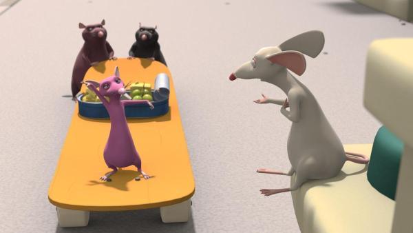 Rattelique (links) steht auf einem Skateboard, dass am Ende von zwei Ratten geschoben wird. Darauf steht mittig eine Blechdose mit Käse und Trauben. Rechts steht ihr Bruder Ratterich und schaut zu. | Rechte: 2021 Caligari Film