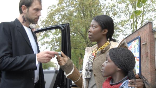 Der Schleuser (Alexander Wüst) treibt Schwarzgeld von Bisa (Dayan Kodua) und ihrer Tochter Acai (Amanda Adjei) ein. | Rechte: NDR/Romano Ruhnau