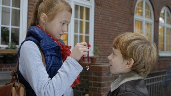 Emma (Aurelia Stern) zeigt Henri (Sammy O'Leary) ein Geschenk von ihremheimlichen Verehrer. | Rechte: NDR/Romano Ruhnau