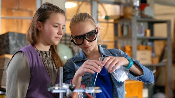 Nina (Carolin Garnier, li.) und Jessi (Martha Fries, re.) in ihrem kleinen Chemielabor im Hauptquartier. | Rechte: NDR/Romano Ruhnau