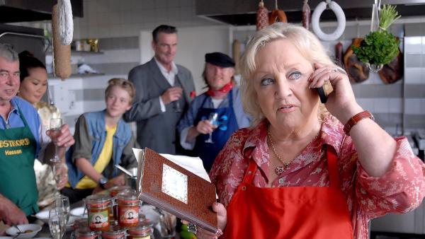 Stolz berichtet Oma Leni (Doris Kunstmann, vorne) dem NDR am Telefon vom Original-Currywurstrezept ihrer Mutter - Enkel Max (Bruno Alexander, hinten Mitte) und die Kollegen sind stolz. | Rechte: NDR/Romano Ruhnau