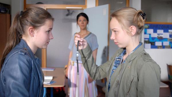 Unter den ungläubigen Blicken ihrer Deutschlehrerin (Katinka Auberger, im Hintergrund) finden Nina (Carolin Garnier, li.) und Jessi (Martha Fries, re.) in der Tasche ihrer Mitschülerin Viki ein fremdes Namensarmband. | Rechte: NDR/Romano Ruhnau