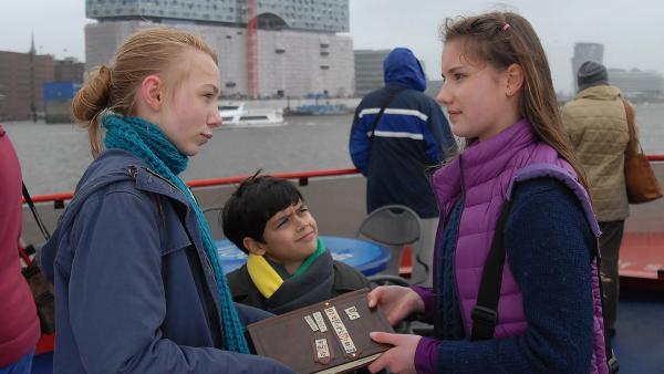 Nina (Carolin Garnier, rechts) übergibt Jessi (Martha Fries, links) und Luis (Emilio Sanmarino, Mitte) das Pfefferkörnerbuch. Sie sollen weitermachen, auch wenn sie nach Italien zieht. | Rechte: NDR/Romano Ruhnau