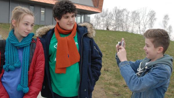 Niklas (Jaden Dreier) mimt mit seiner Kamera den rasenden Reporter für Jessi (Martha Fries) und Anton (Danilo Kamber). | Rechte: NDR/Romano Ruhnau