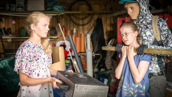 Der maskierte Täter (Luise Wolfram) hat Pinja (Sina Michel) in seiner Gewalt und fordert von Stella (Zoë Malia Moon, links) den Koffer mit den Schmetterlingspuppen zurück.  | Rechte: NDR/Boris Laewen