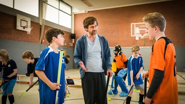 Hockeytrainer John (Andreas Nickl) versucht, den Streit zwischen Ramin (Jann Piet, links) und Tom (Vincent Grages) zu schlichten. | Rechte: NDR/Boris Laewen