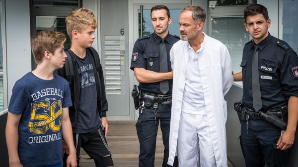 Noch immer wütend beobachten Till (Otto von Grevenmoor, 2. v. l.) und Marvin (Lewin Winter, li.), wie Dr. Götze (Matthias Leja, Mitte) abgeführt wird. Zu Recht! | Rechte: NDR/Boris Laewen