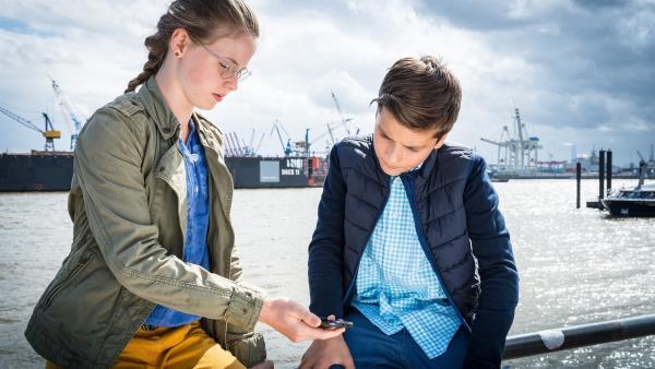 Pinja (Sina Michel, li.) und Ramin (Jann Piet, re.) kriegen eine wichtige Nachricht per SMS. | Rechte: NDR/Boris Laewen