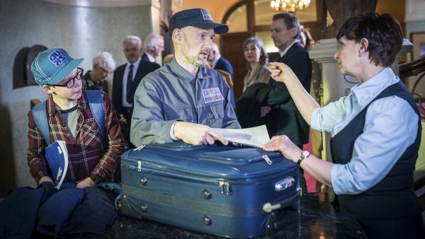 Benny (Ruben Storck, links) recherchiert im Auktionshaus und beobachtet, wie ein Lieferant (Timo Werner) einen mysteriösen Koffer bei der Garderobiere (Annette Bajorat) abliefert. | Rechte: NDR/Boris Laewen