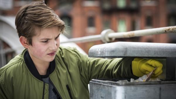 Johannes (Luke Matt Röntgen) durchsucht fieberhaft die Mülleimer in der Umgebung des Cafés nach Indizien. | Rechte: NDR/Boris Laewen