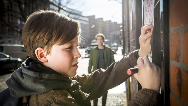 Johannes (Luke Matt Röntgen) beobachtet, wie ein mysteriöser Junge (Nikita Lysko, vorn) vorm Café Nachrichten auf einen Zettel kritzelt. | Rechte: NDR/Boris Laewen