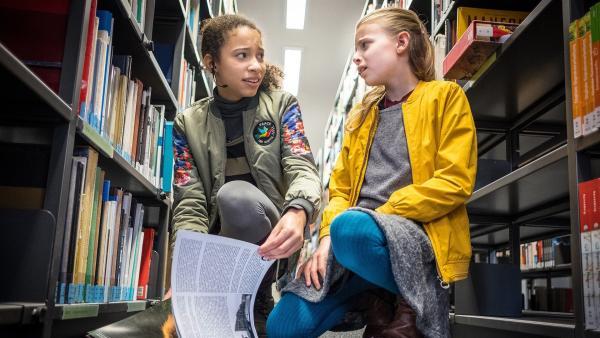 Lisha (Emma Roth, links) und Alice (Emilia Flint, rechts) verstecken das Schweigegeld für den Erpresser in einem Buch und starten mit ihrer Observation. | Rechte: NDR/Boris Laewen