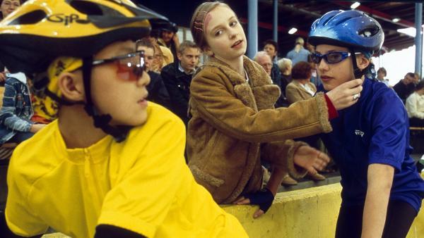 Panda (Tim Patrick Chan) und Paul (Lukas Decker) nehmen an einem Fahrradrennen teil. Vivi (Aglaja Brix) passt auf, dass Pauls Sturzhelm sitzt. Paul muss sich im entscheidenden Finalrennen dem mutmaßlichen Saboteur stellen. | Rechte: NDR/Sandra Höver