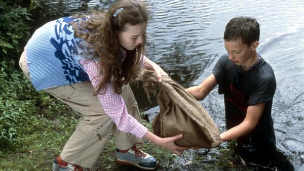 Paul (Lukas Decker) und Katja (Jana Fomenko) retten einen kleinen Hund aus dem See, den einfach jemand in einen Sack gestopft und ins Wasser geworfen hat. | Rechte: NDR/Sandra Hoever